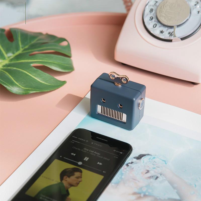 enceinte bluetooth robot bleu sur une table rose
