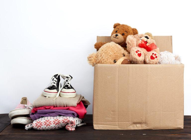 pile de vêtements à donner avec un carton d'objets