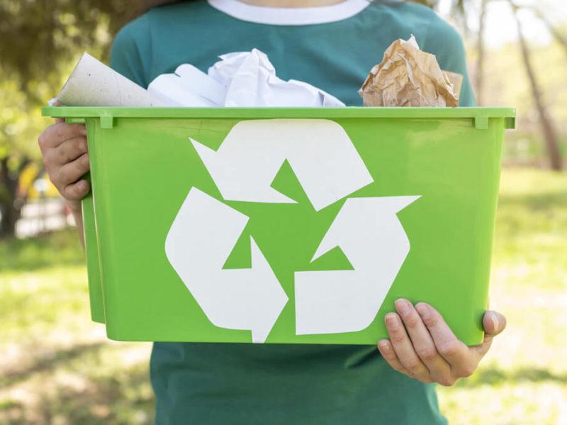 Homme tenant une poubelle de recyclage