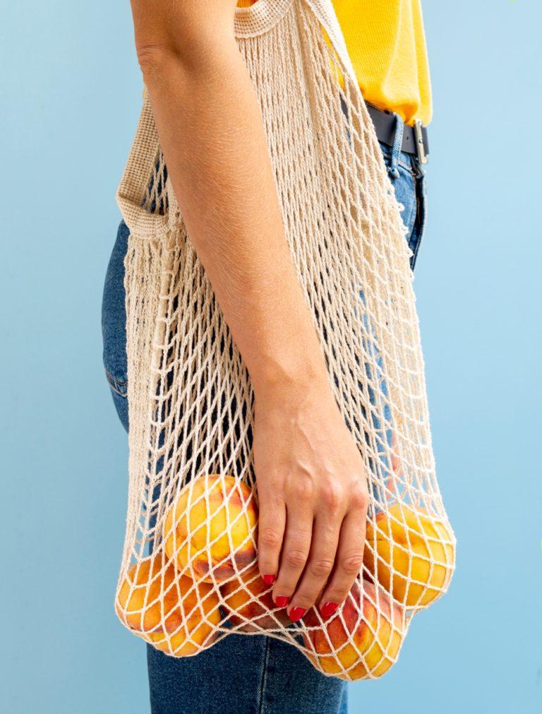 femme portant un tote bag avec des oranges